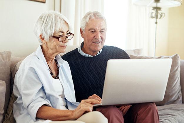 Äldre par söker info via dator