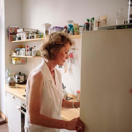 Kvinna tittar i kylskåp