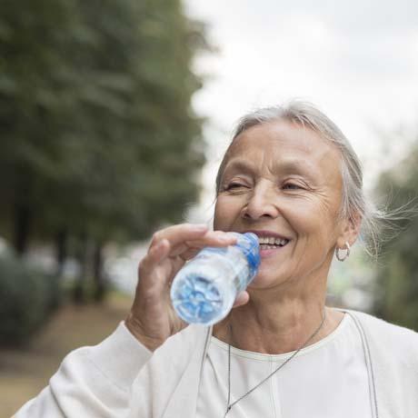 Kvinna dricker ur vattenflaska